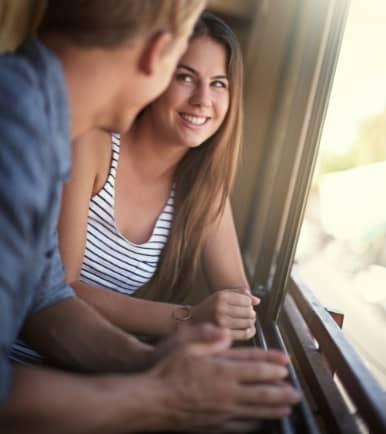 Hombre con una mujer cerca de una ventana conversando