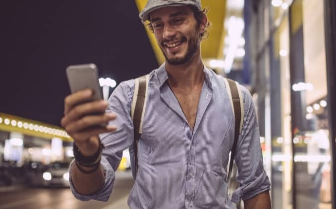 Hombre de personalidad y apariencia atractiva caminando en la calle recibiendo un mensaje de texto de una chica